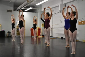 teen dancers in a studio posing with arms in fifth position.