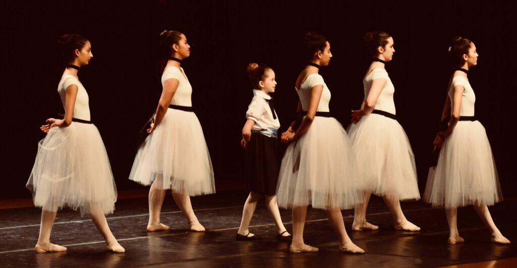 "Dancers dressed like Degas ""Little Dancer' pose in fourth position."