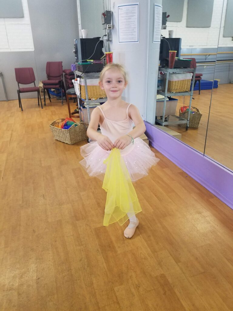 a young dancer stands holding a yellow scarf