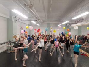 dancers with balloons jumping in the air.