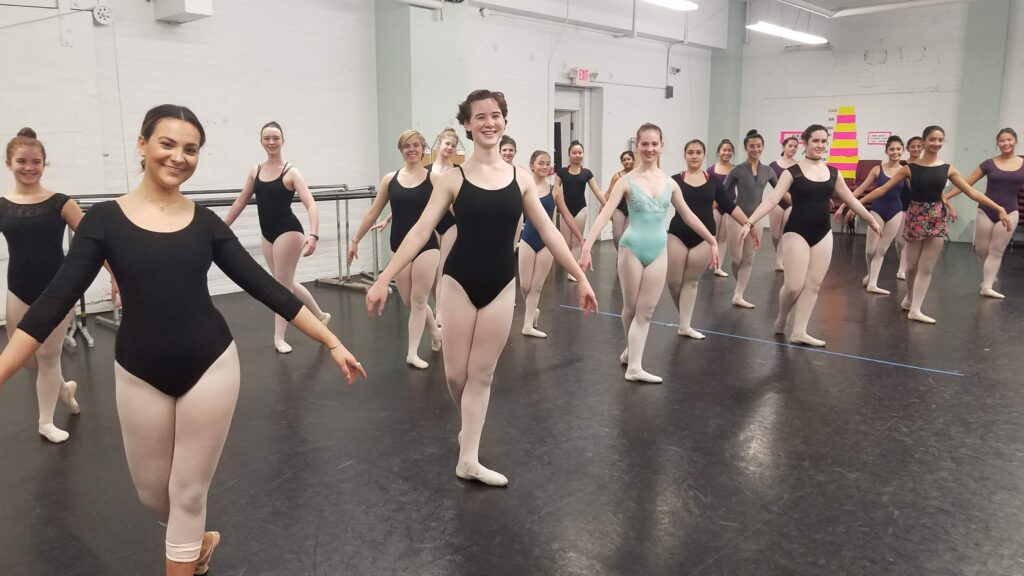 dancers standing in class in a b-plus position