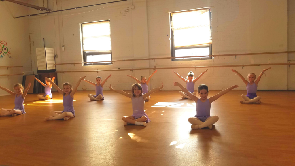 young dancers seated with arms in a high V position