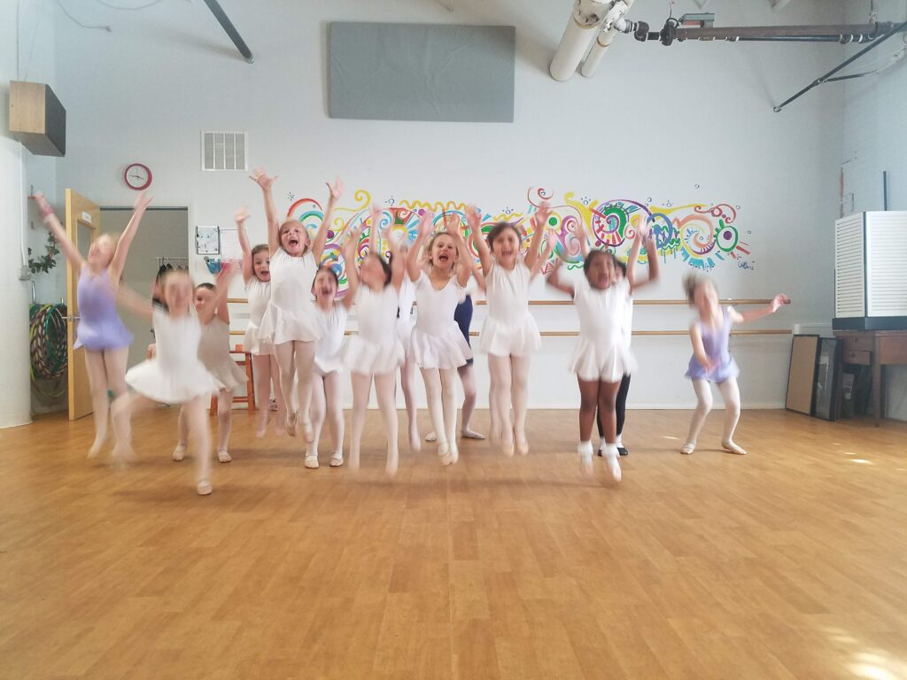 young dancers in a studio jumping for joy.