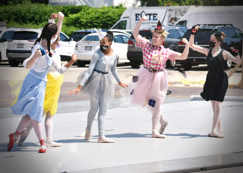 Dancers dressed as Dorothy, Lion, Tinman, Scarecrow and Toto in an outdoor performance.