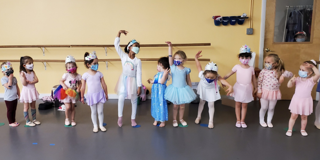 young dancers wait for their turn, wearing masks, hand-made crowns, and ballet clothes and costumes.